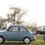 Woman pushes her Fiat 500 car as her dog sits inside, in neighbourhood of Rome